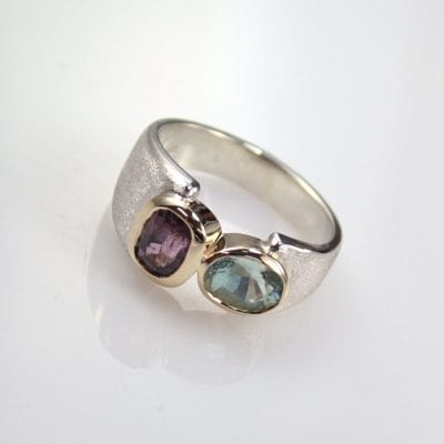 This gorgeous contemporary coloured stone ring design features two beautiful pastel coloured gemstones. Sky Blue Aquamarine,and Mauve Spinel, set in 9ct Yellow Gold with Silver Palladium. We use Silver Palladium as an alternative to Sterling Silver because it will not tarnish, retaining its gorgeous bright whit colour. We have used Bezel settings both to highlight the clean flowing lines of this ring and to help protect the gemstones. Designed to maximise comfort the band of this ring features a beautiful soft rounded profile. About Aquamarine and Spinel Aquamarines are a very popular stone accross many cultures. They are also the symbolic birthstone of March, and ranges in colour from sea-foam green, to sky-blue, to teal. Aquamarine is part of the Beryl mineral family and has a hardness of 8 onthe Moh's Scale of hardness. A slightly lesser known gemstone, Spinel has gained in popularity quickly since the crown jewels have been discovered to feature a Spinel as the centre piece! Spinel has also become known as the modern birthstone of August. The gem world is quickly being captivated by the vast array of colours Spinel can be found in. Most commonly found in Red, Pink, Blue, Purple and Orange. Spinel also has a hardness of 7.5-8 onthe Moh's Scale of hardness. The properties of Aquamarineand Spinel, alongside the modern bezel settings make this bespoke design ideal for everyday wear. Designed and handcrafted in the beautiful Sunshine Coast Hinterland. Right here in our onsite jewellery workshop, by master goldsmith Ishkhan Kojayan. This designer ring is available for viewing in the comfort ofour gallery in the heart of Montville, Sunshine Coast Hinterland. Reference Code: LJ-R293