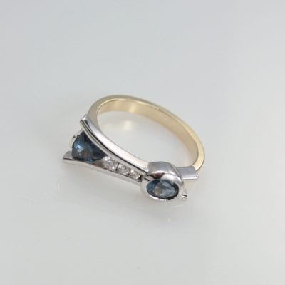 This designer contemporary style  features a two stunning Blue Spinels set in 9ct White Gold.  Ethically sourced from one of the most prominent mines of tourmaline in the world, located in Sri Lanka.  The 3x Round Brilliant Cut G/SI Diamonds (measuring 2.4mm, 2.0mm, 1.5mm) that appear to be floating between two plates of White Gold are truly a statement in their own right. Crafted in 9ct Yellow Gold, the band of this ring is simplistic and elegant. About Spinel and Diamond A slightly lesser known gemstone, Spinel has gained in popularity quickly since the crown jewels have been discovered to feature a Spinel as the centre piece! Spinel has also become known as the modern birthstone of August. The gem world is quickly being captivated by the vast array of colours Spinel can be found in. Most commonly found in Red, Pink, Blue, Purple and Orange.  Spinel also has a hardness of 7.5-8 on the Moh's Scale of hardness. Whilst  Diamonds have a hardness of 10/10 on the Moh's Scale of hardness – second to none. We love diamonds for their exceptional brilliance and ability to reflect light. This is the reason why they are so sparkly! The properties of Spinel and Diamonds alongside the modern setting make this bespoke design ideal for everyday wear. Designed and handcrafted in the beautiful Sunshine Coast Hinterland. Right here in our onsite jewellery workshop, by master goldsmith Ishkhan Kojayan. This designer ring is available for viewing in the comfort of our gallery in the heart of Montville, Sunshine Coast Hinterland. Reference Code: LJ-R296