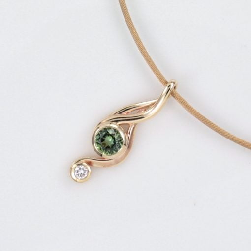This gorgeous organic flowing Pendant design features a beautiful Round Cut Apple Green Tourmaline. Accompanied by a dazzling 0.20ct Round Brilliant Cut Diamond and together set in 9ct Yellow Gold.  We have used Bezel settings to help highlight the clean flowing lines of this pendant and these gorgeous hero gemstones.